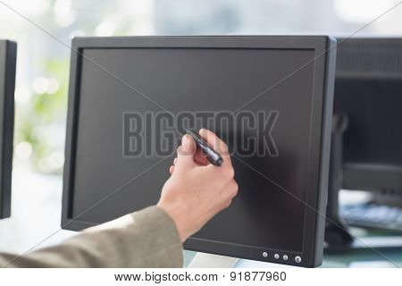 Businesswoman touching computer screen with pen in office