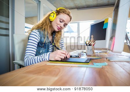 Smiling designer working with digitizer and listening music in the office
