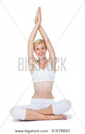 Fit smiling woman meditating on white background