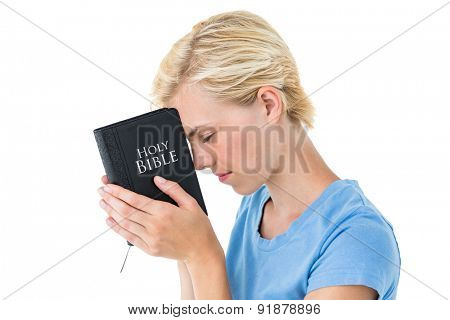 Pretty blonde woman holding bible on white background