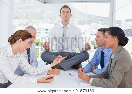 Businessman relaxing on the desk with upset colleagues around in the office