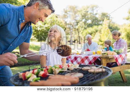 Happy father doing barbecue with her daughter on a sunny day