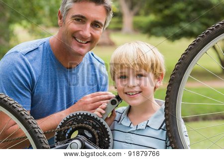 happy father and his son fixing a bike on a sunny day