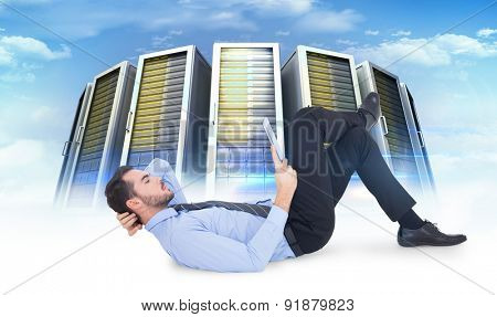 Businessman lying on floor using tablet against composite image of server towers