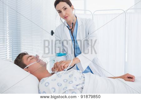 Smiling doctor auscultating her patients chest in hospital room