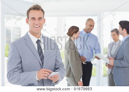 Businessman texting while his colleagues discussing in the office