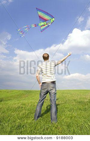 Joven parado en el césped de verano y jugando con cometas multicolores, vista desde la parte posterior