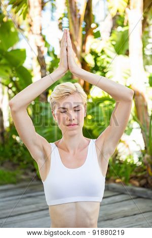 Pretty fit blonde woman meditating outside on a sunny day