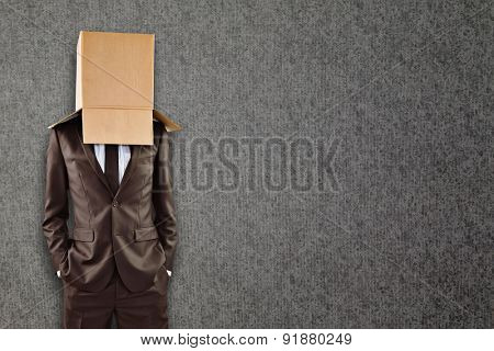 Anonymous businessman with hands in pockets against grey background