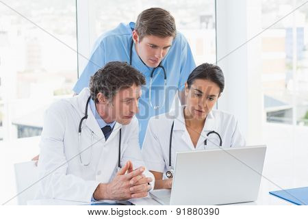Team of doctors working on laptop computer in medical office