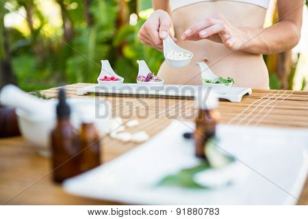 Fit woman holding plate with herbal medicine outside on a sunny day
