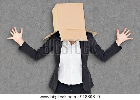 Anonymous businesswoman with her hands up against grey background