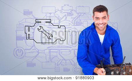 Smiling male machanic repairing car engine against grey vignette