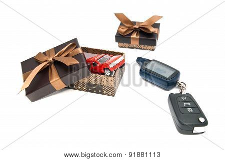 Red Car, Keys And Brown Gift Boxes On White