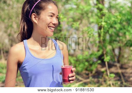 Healthy Asian woman drinking fruit smoothie drink in outdoor forest park during summer. Young fit girl holding plastic cup clean eating for detox cleansing with berry or beet juice as part of a diet.