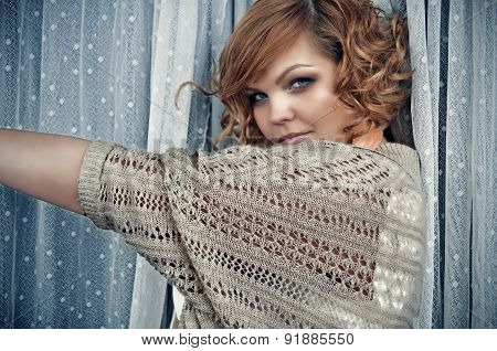 Mysterious trendy woman with short curly red hair standing between white long dotted lace curtains.