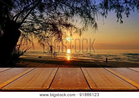Outdoor Picnic Background With Wooden Table On Sea Pine Beach At The Sunrise.