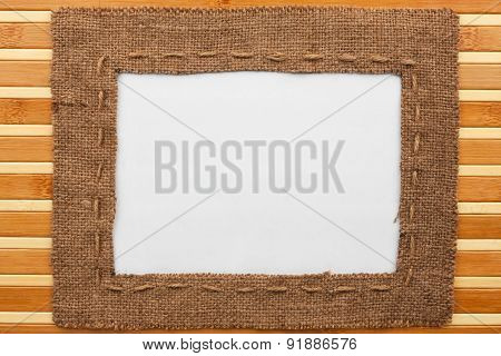Frame Made Of Burlap With White Background Lying On A Bamboo Mat