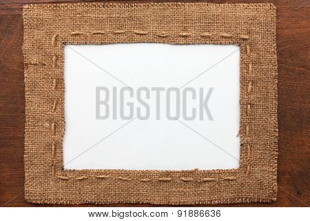 Frame Made Of Burlap With White Background Lying On A Wooden Surface