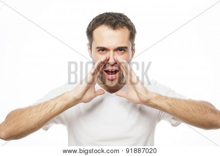 people, emotions and lifestyle concept -  handsome man in white t-shirt  shouting while looking at camera and standing against white background