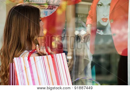 SERBIA - MAY 23: Close up shot of a teenage girl with shopping bags standing next to a boutique window and looking wardrobe in Lazarevac, Serbia.