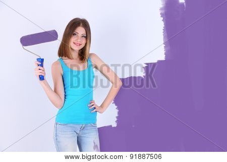 Beautiful girl with roller near wall