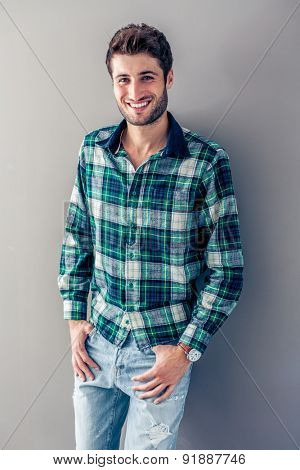 Handsome young man smiling in front of a grey wall