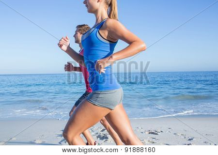 Happy couple running together beside the water at the beach