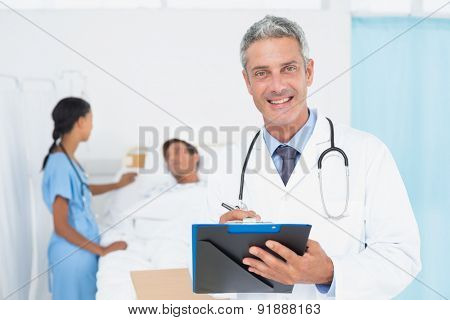 Doctor with colleagues and patient behind in the hospital