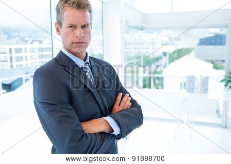 Serious businessman looking at camera in his office