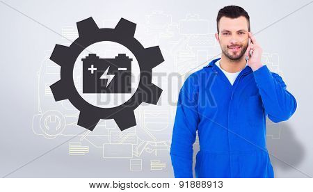 Smiling male mechanic using his mobile phone against grey vignette