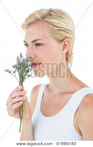 Gorgeous blonde woman smelling flowers on white background