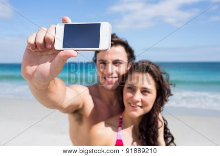 Happy couple taking selfie at the beach