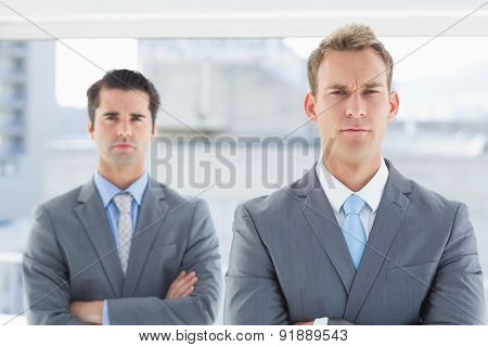 Two businessmen frowning at camera in the office