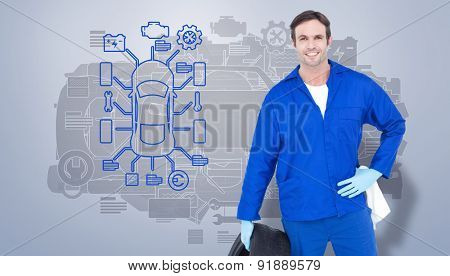 Mechanic holding tire while standing with hand on hip against grey vignette
