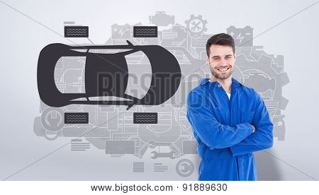 Smiling young male machanic standing arms crossed against grey vignette