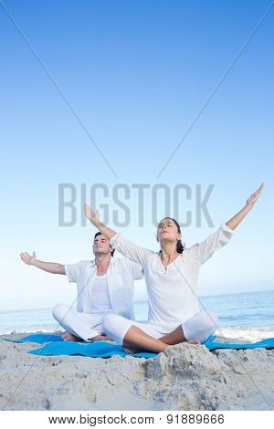 Happy couple doing yoga beside the water at the beach