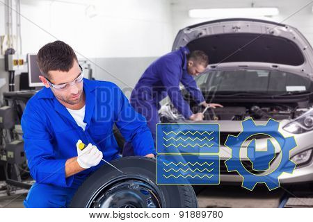 Mechanic working on tire over white background against mechanic leaning on a car looking at the engine