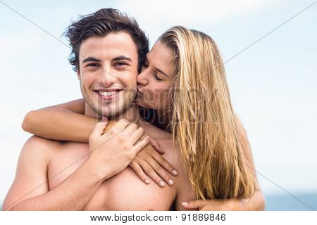 Handsome man receiving kiss from his gilfriend at the beach