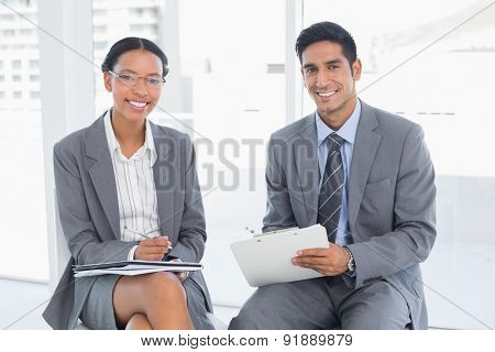 Two young business people in board room meeting at office