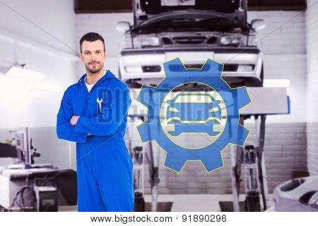 Smiling male mechanic holding spanner against auto repair shop