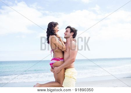 Happy couple hugging and looking at each other at the beach