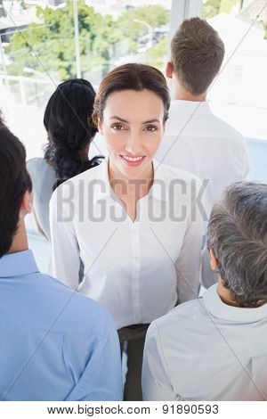 Smiling businesswoman with colleagues back to camera in the office