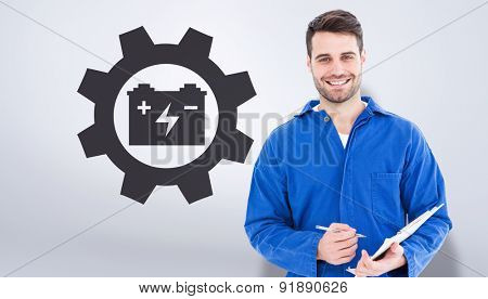 Smiling male mechanic writing on clipboard against grey vignette