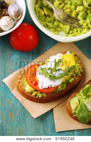 Tasty sandwich with egg, avocado and vegetables on paper napkin, on color wooden background