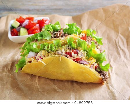 Tasty taco with vegetables on paper close up