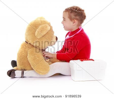 Funny little girl playing doctor with a Teddy bear