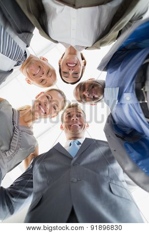 Business colleagues standing in circle and looking at camera in the office