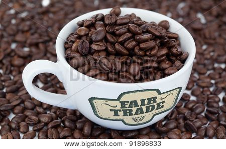 Fair Trade graphic against small white cup of coffee beans