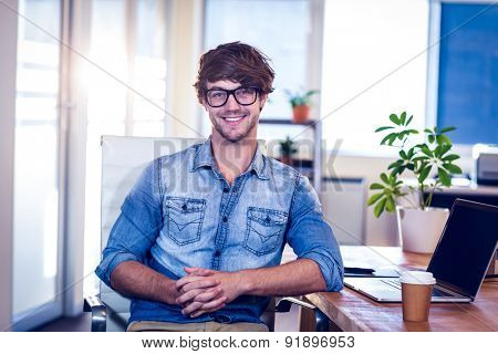 Happy designer smiling at camera in creative office